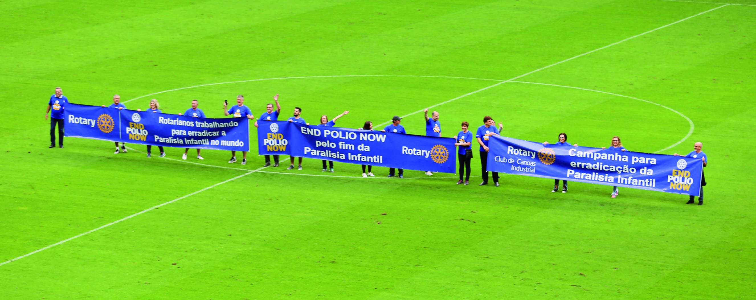 Rotary members in District 4670 carried an End Polio banner out on a football field.